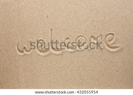 Welcome is the inscription by hand on the sand, view from above - stock photo