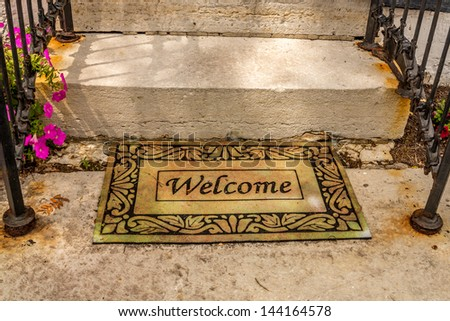 Welcome mat sitting at the bottom of a set of stairs with black hand rails and flowers