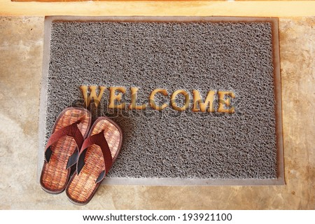 welcome mat with brown sandals on floor - stock photo