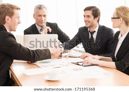 Welcome on board! Four business people sitting at the table while two of them shaking hands and smiling - stock photo