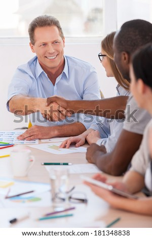 Welcome on board! Group of business people sitting in a row at the table while two men handshaking - stock photo