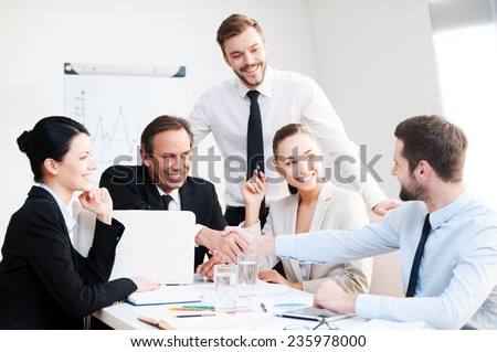 Welcome on board! Group of confident business people in formalwear sitting at the table together and smiling while two men handshaking  - stock photo