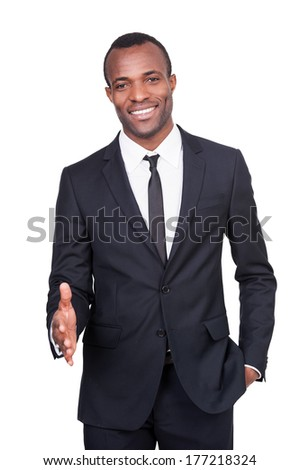 Welcome on board! Handsome young African man in full suit stretching out hand for shaking and smiling while standing isolated on white background  - stock photo