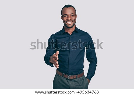 Welcome on board! Handsome young African man stretching out hand for shaking and smiling to you while standing against grey background