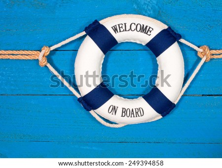 Welcome on Board - Lifebuoy with text on blue wooden background - stock photo