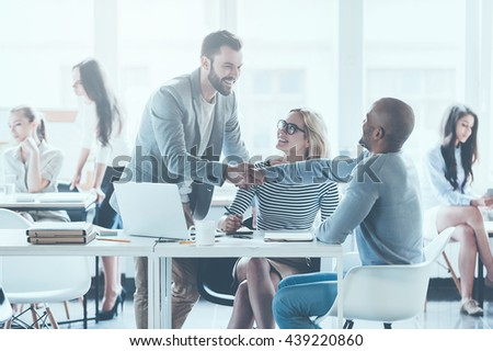 Welcome on board! Two cheerful young man shaking hands while being in office together with their colleagues  - stock photo