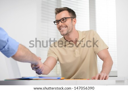 Welcome on board! Young cheerful businessman shaking someone's hand and smiling - stock photo