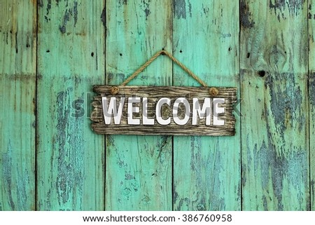 Welcome sign hanging on antique rustic mint green wood background