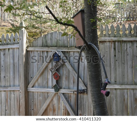Welcome sign on a weathered wooden garden fence gate, with garden hose hanging in tree , slightly out of focus, in foreground. - stock photo