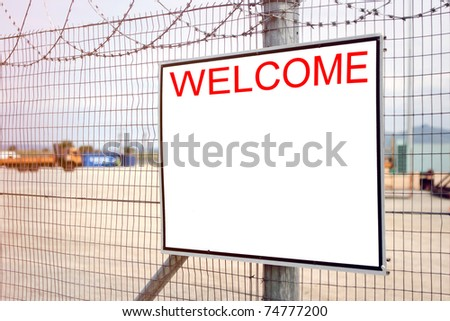 Welcome sign on industrial fence - stock photo