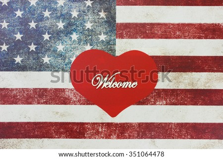 Welcome sign on red heart with rustic American canvas flag blurred in background - stock photo