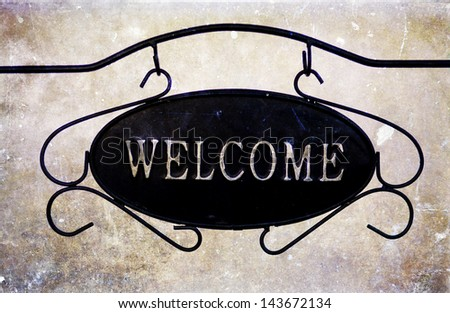 Welcome sign on vintage background - stock photo