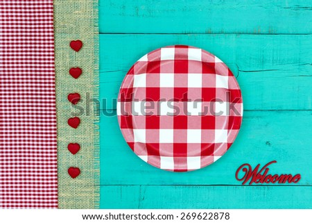 Welcome sign with red and white checkered plate, hearts and gingham and burlap border on antique teal blue wood background; above view looking down - stock photo