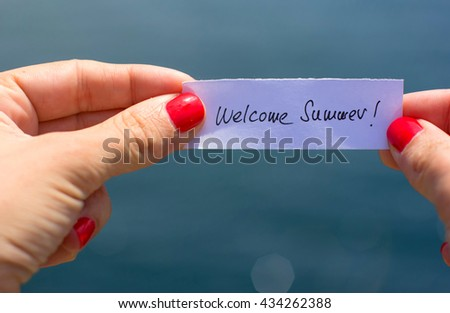 Welcome Summer contept. Woman hands holding a piece of paper with summer message