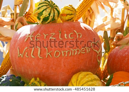 Welcome! text in German on autumn  pumpkins