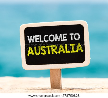 Welcome to Australia on chalkboard. Welcome to Australia text written on chalkboard, on beach - stock photo