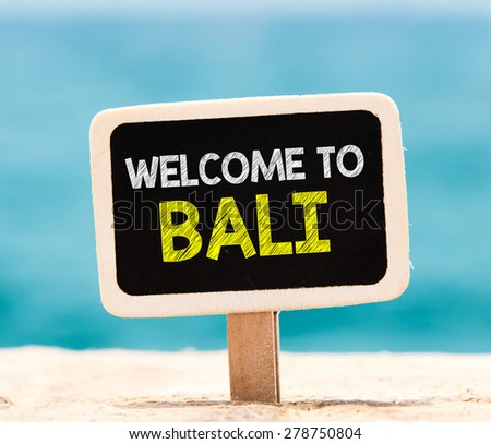 Welcome to Bali on chalkboard. Welcome to Bali text written on chalkboard, on beach - stock photo