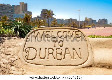 Welcome to Durban sand sculpture with skyline of Durban waterside in the background