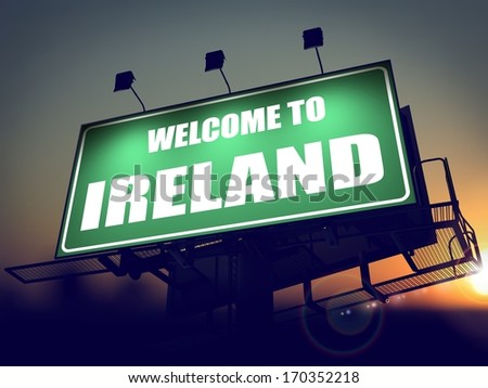 Welcome to Ireland - Green Billboard on the Rising Sun Background. - stock photo