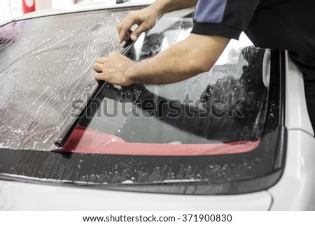 Welcome to our car service station. Closeup image of a car mechanic man attaching tinting film foil to car window in specialized service station - stock photo