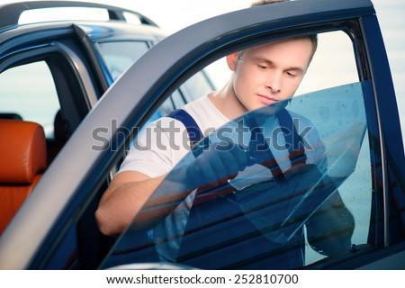 Welcome to our car service station. Closeup image of a handsome car mechanic attaching tinting foil to car window and smiling at camera in specialized service station