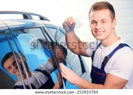 Welcome to our car service station. Closeup image of a handsome car mechanic attaching tinting foil to car window and smiling at camera in specialized service station - stock photo