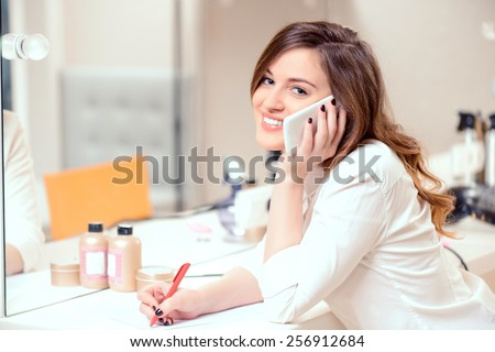 Welcome to our salon. Side view portrait of a beautiful smiling administrator of hairstyle salon speaking over the mobile phone and putting down details of the order   - stock photo