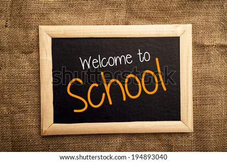 Welcome to school note on black message board - stock photo