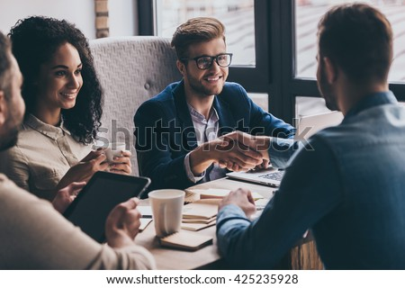 Welcome to team! Two men shaking hands and looking at each other with smile while their coworkers sitting at the business meeting  - stock photo