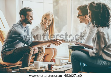 Welcome to team! Two men shaking hands and smiling while sitting together with their coworkers in office