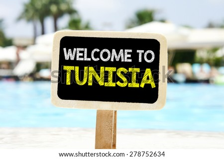Welcome to Tunisia on chalkboard. Welcome to Tunisia text written on chalkboard near pool - stock photo