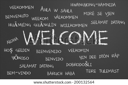 Welcome word cloud written in many different languages on a chalkboard - stock photo