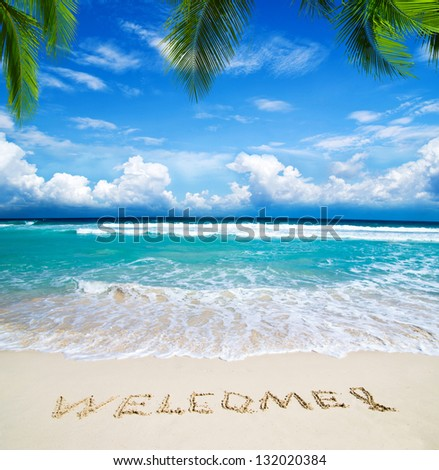 welcome written in a sandy tropical beach - stock photo