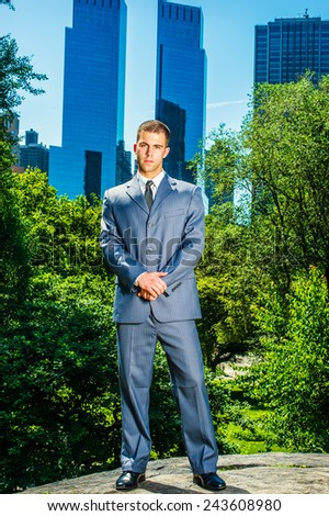 Welcome you to big city. Dressing formally in a blue suit, leather shoes, short haircut, holding hands, a young handsome professional standing in the front of business district, waiting for you. - stock photo
