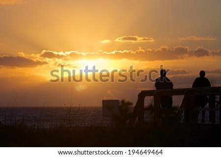 Welcoming a New Day  Picture of the silhouette of a two seniors on a Florida boardwalk watching the sunrise over the ocean. - stock photo