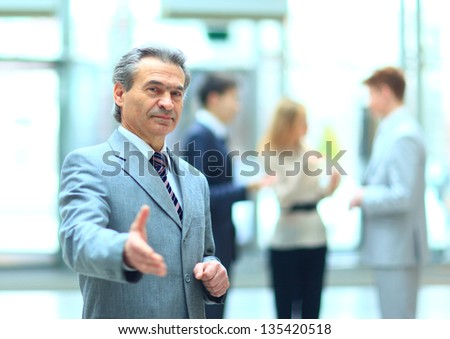 Welcoming business man ready to handshake with hand extended - stock photo
