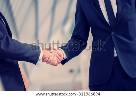 Welcoming business partners Handshake. Two successful businessman sitting at the table looking at each other shaking hands - stock photo