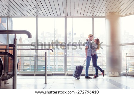 Welcoming embrace. Young loving couple hugging in the airport terminal. - stock photo
