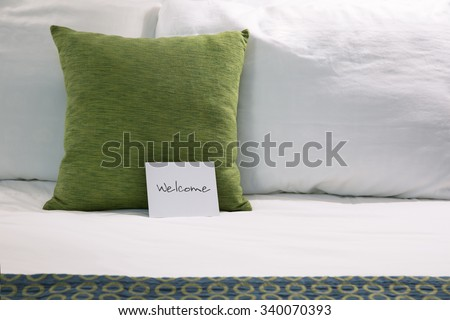 Welcoming hotel bed with pillows and welcome card close up.