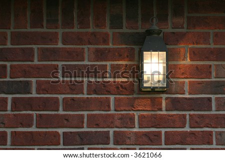 welcoming porch light on brick wall - stock photo
