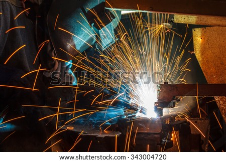 Welder and bright sparks. Construction and manufacturing - stock photo
