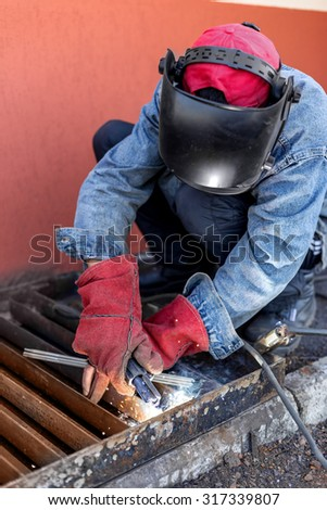 Welder at work. Welder cooks metal grate on the ground blowtorch on the ground in special clothes and mask welder. Selective Focus