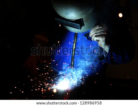 Welder at work with welding mask and torch