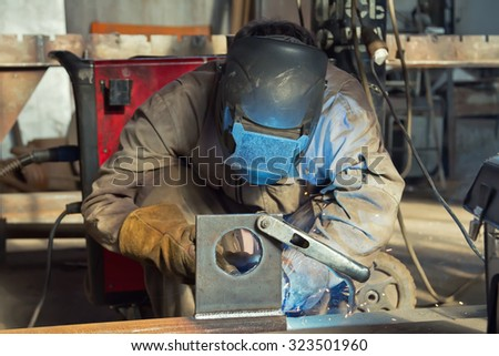 Welder in the mask and protective clothing is gaining increased cladding weld - stock photo
