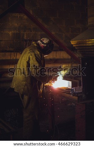 Welder in work clothes. Concrete products plant, working in the welding shop