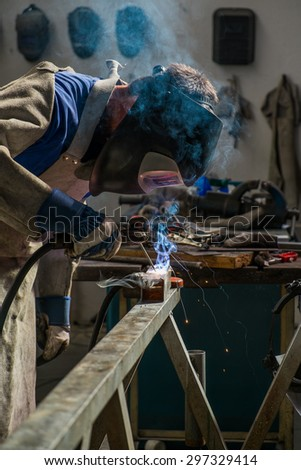 Welder in workshop manufacturing metal construction