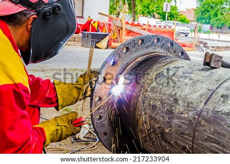 Welder is welding a pipe in a trench. - stock photo