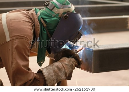welder is welding end plate of steel pipe with all safety equipment in factory - stock photo