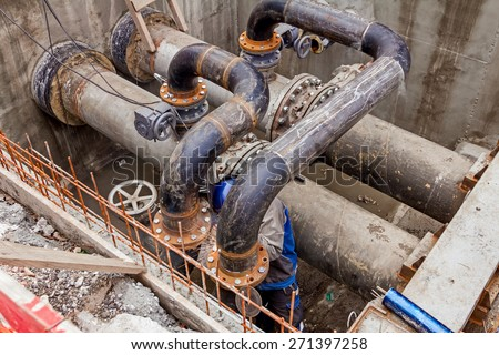 Welder is welding pipe junction completing a manhole for heating pipeline system - stock photo