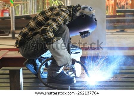welder is welding steel structure with all safety equipment in factory - stock photo
